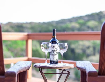 wine bottle and glasses on porch table